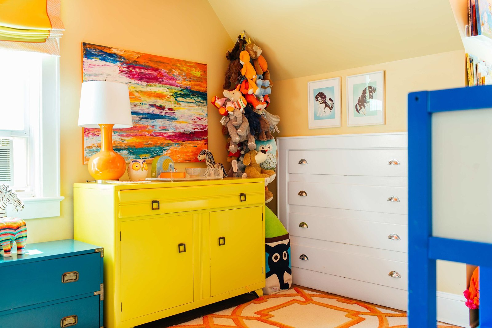 A boys bedroom with a yellow dresser and built in white dresser.
