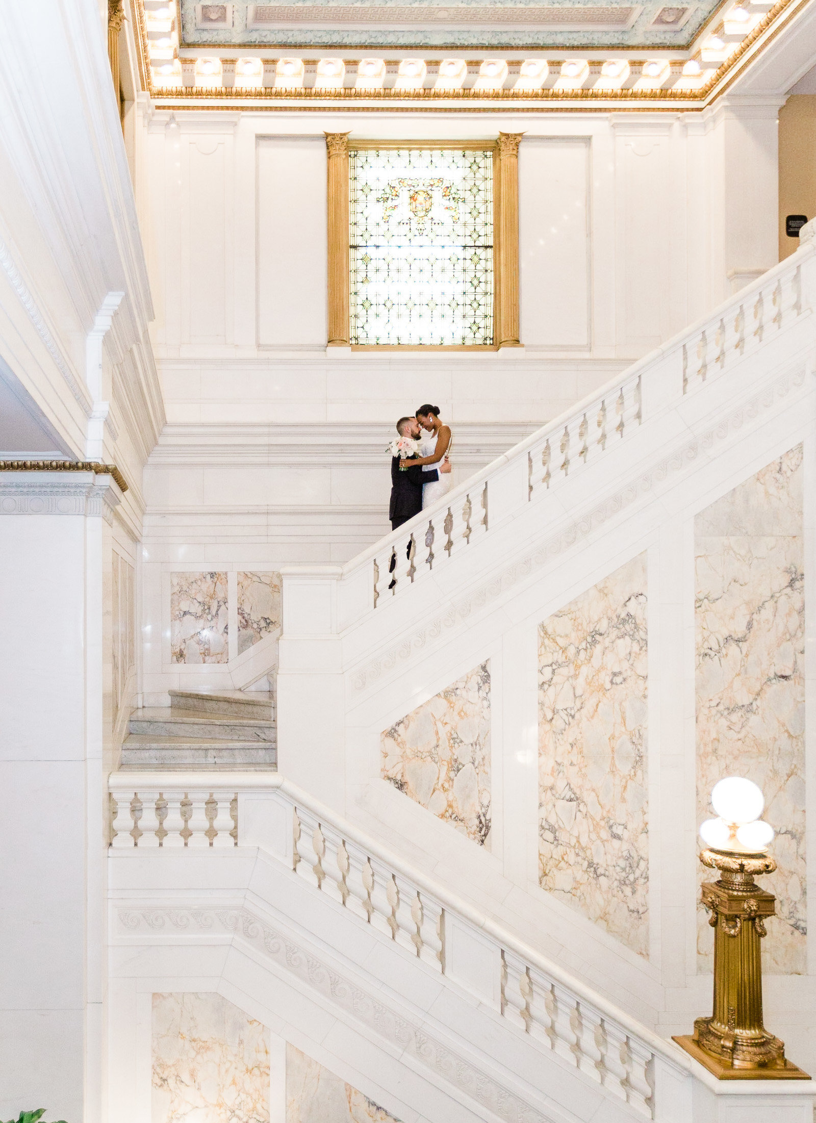 Bride and groom on grand white marble staircase at the kimpton hotel Monaco