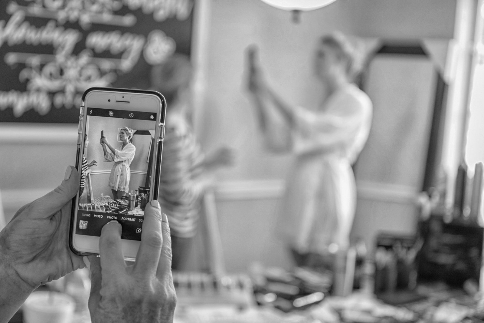 bride looks at herself while mother of the bride takes a picture on her phone