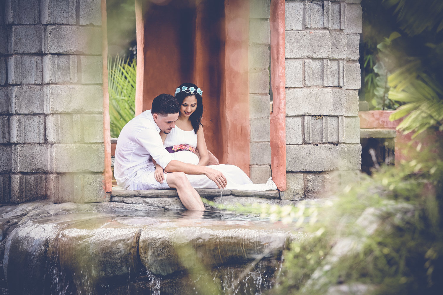 Pregnant couple sit together in idyllic setting. Photo by Ross Photography, Trinidad, W.I..