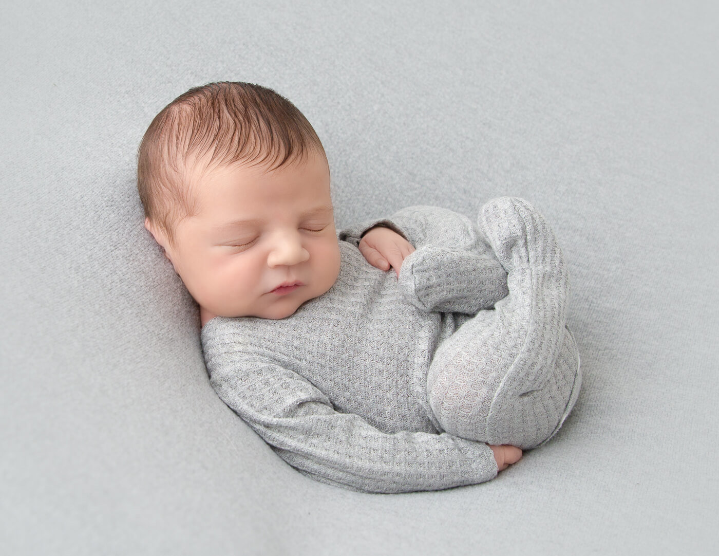 Newborn baby boy posed in our Rochester, NY studio.
