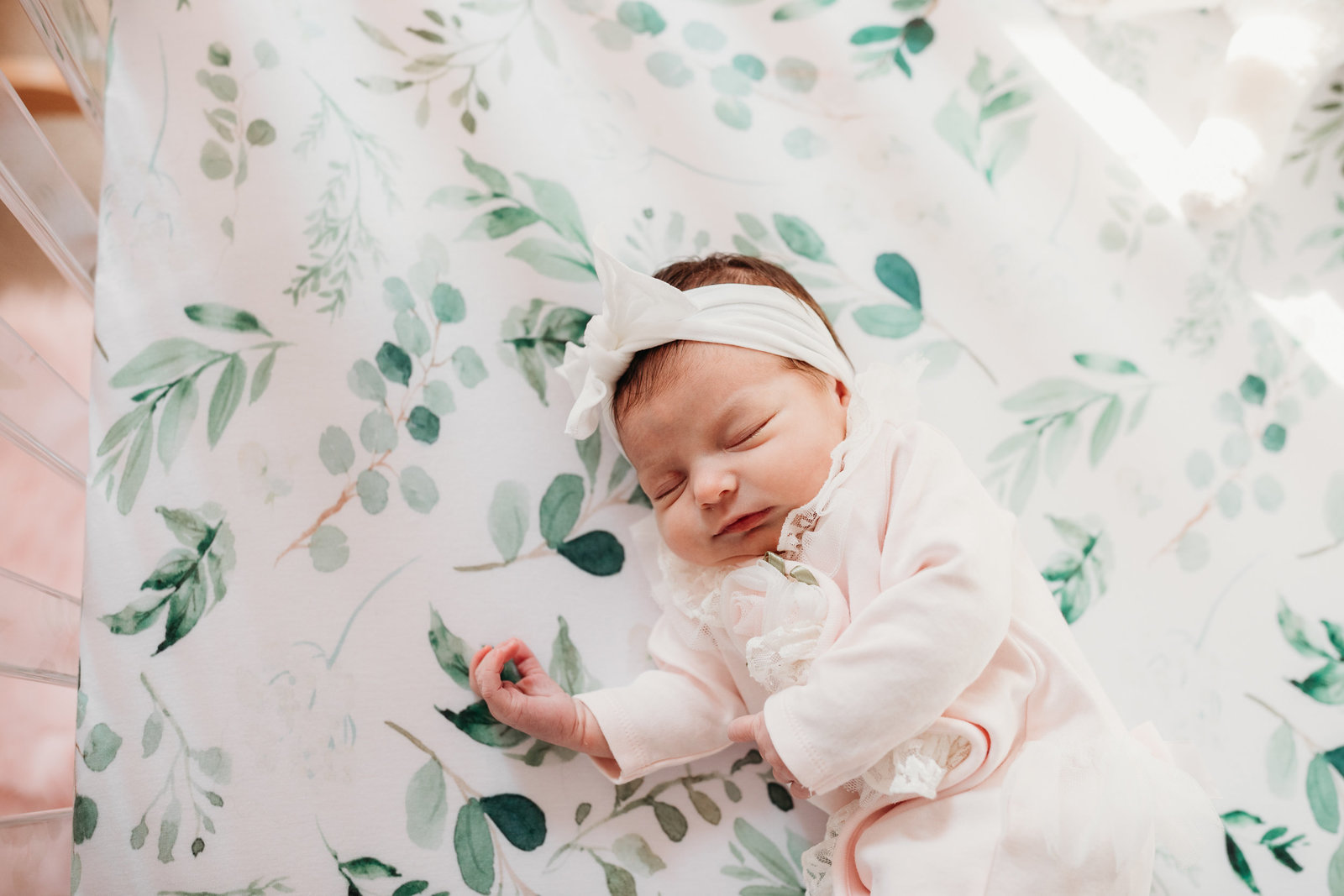 baby girl lies on beautiful crib bedding with leaves