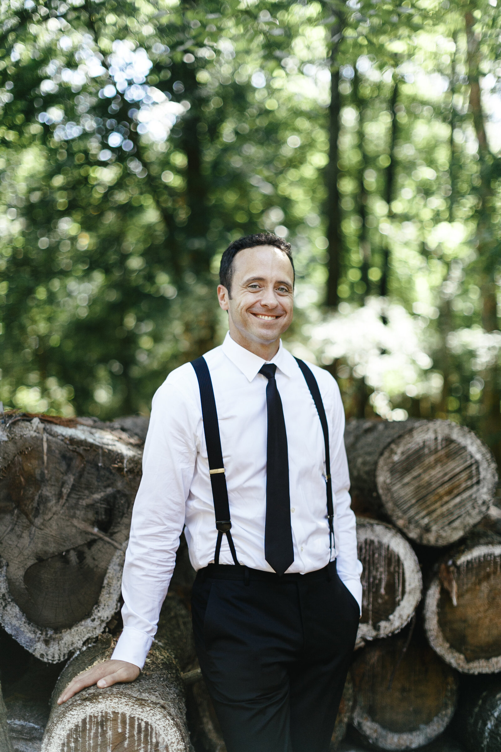 groom with suspenders at farm with wood pile