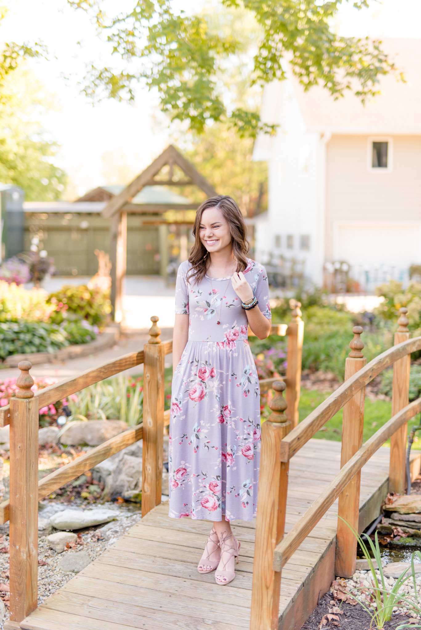 senior stands on bridge in floral dress