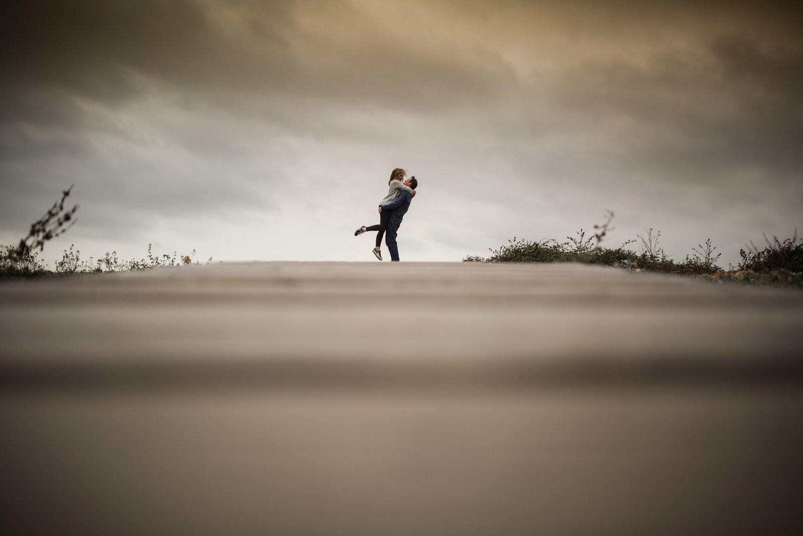 An engaged man stand on wooden path on a beach in Norfolk and lifts his fiance into the air. The beach is looking stormy and grey.