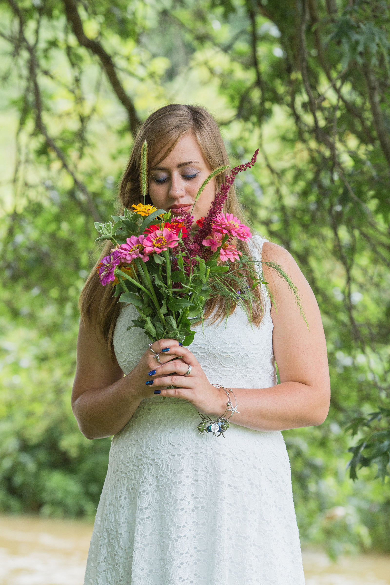 senior girl holds bouquet of wild flowers as she stand in front of a creek