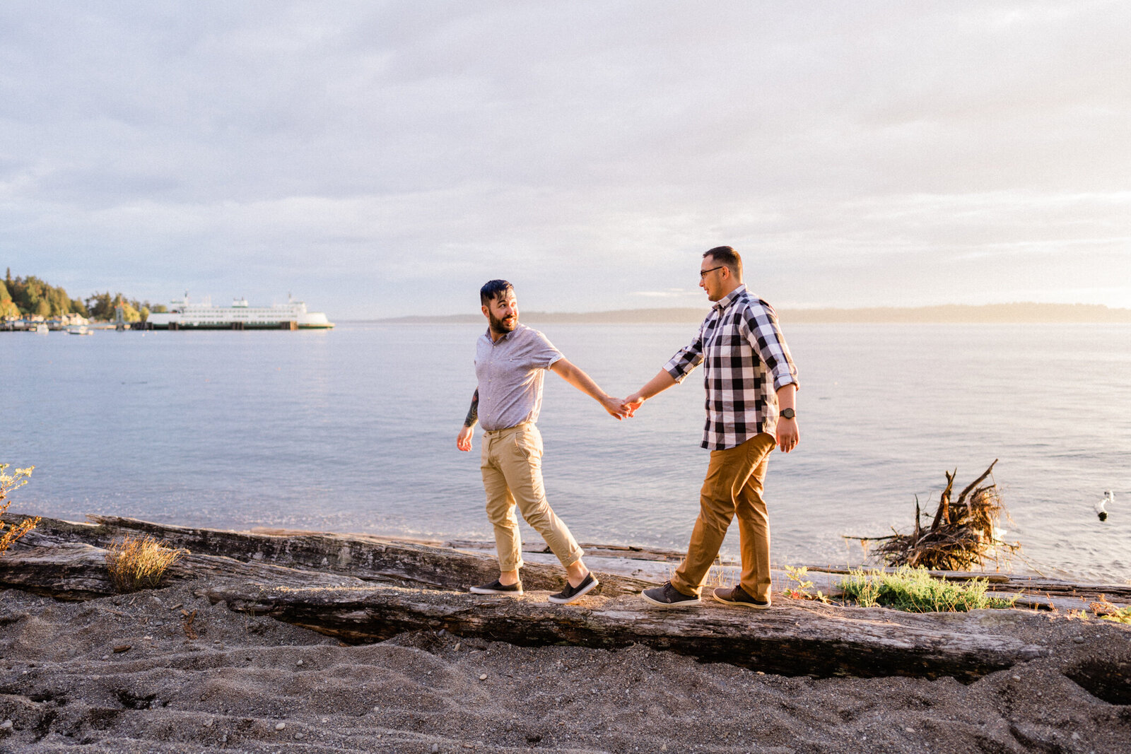 Couple holding hands along Puget Sound beach at Lincoln Park in West Seattle, one of the best spots for engagement photos in Seattle.
