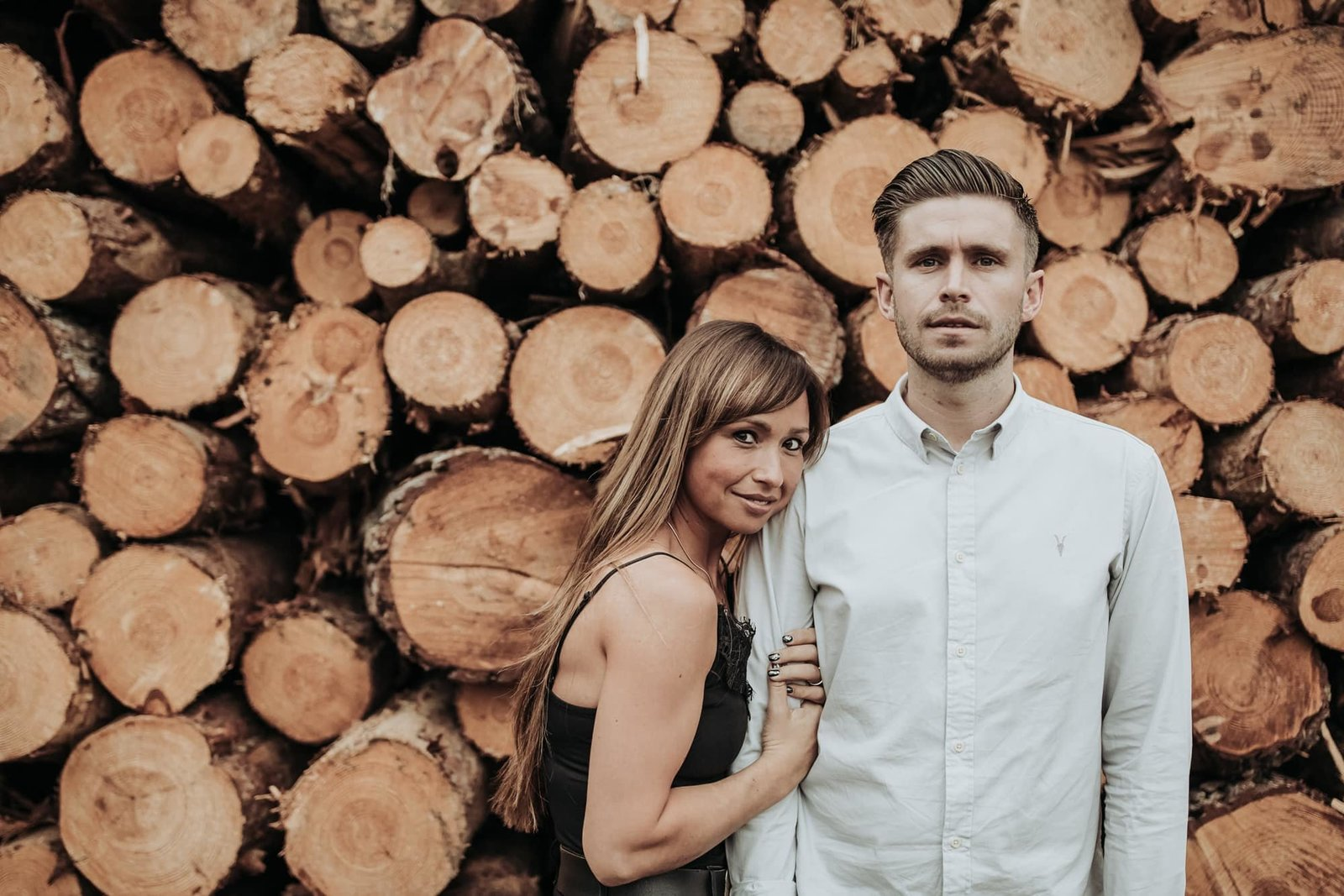An engaged couple stand in front of cut timber in a Norfolk forest, the lady holds her future husbands arm.