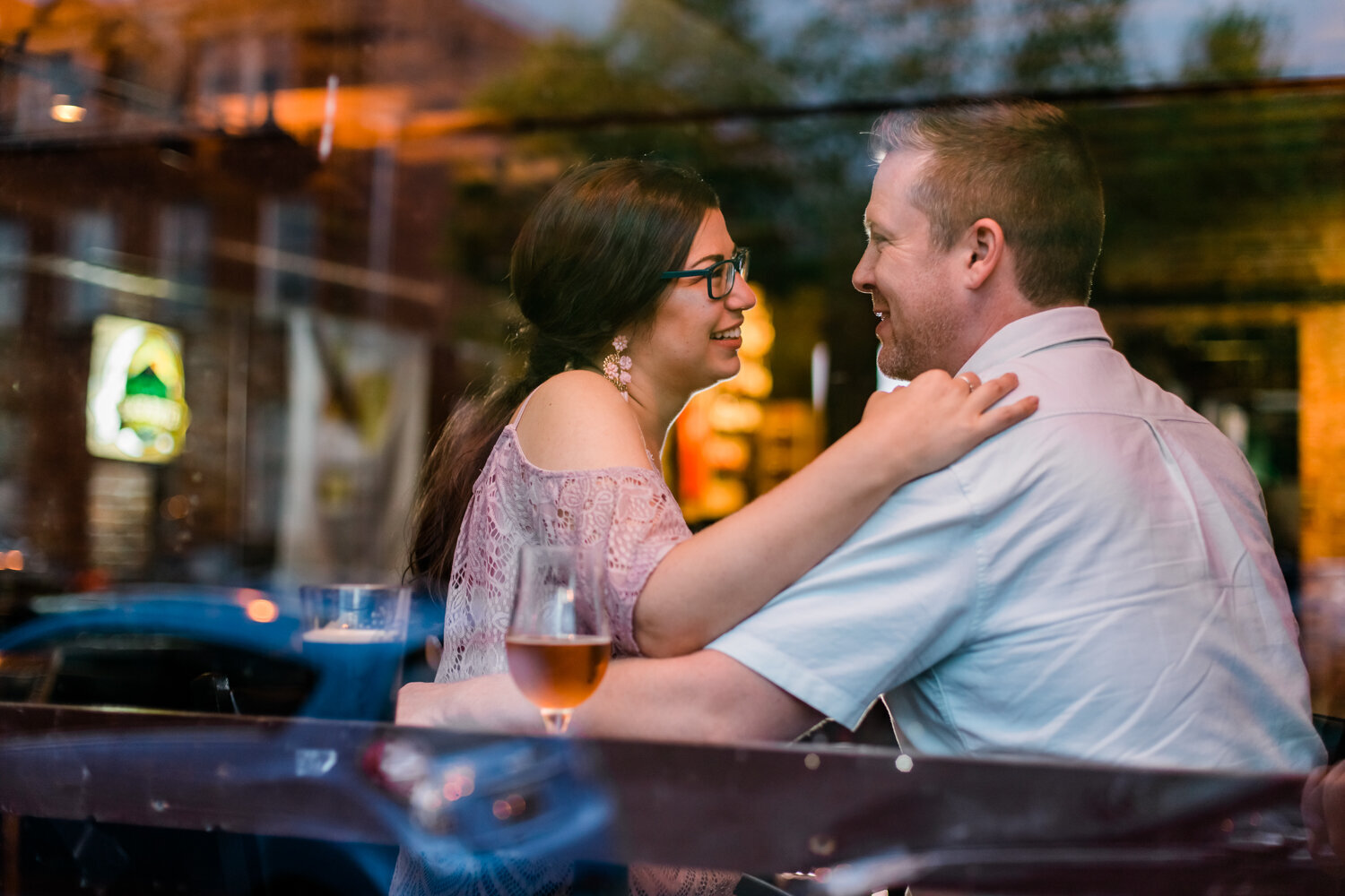 Engagement photo taken through the window at a bar in St. Louis