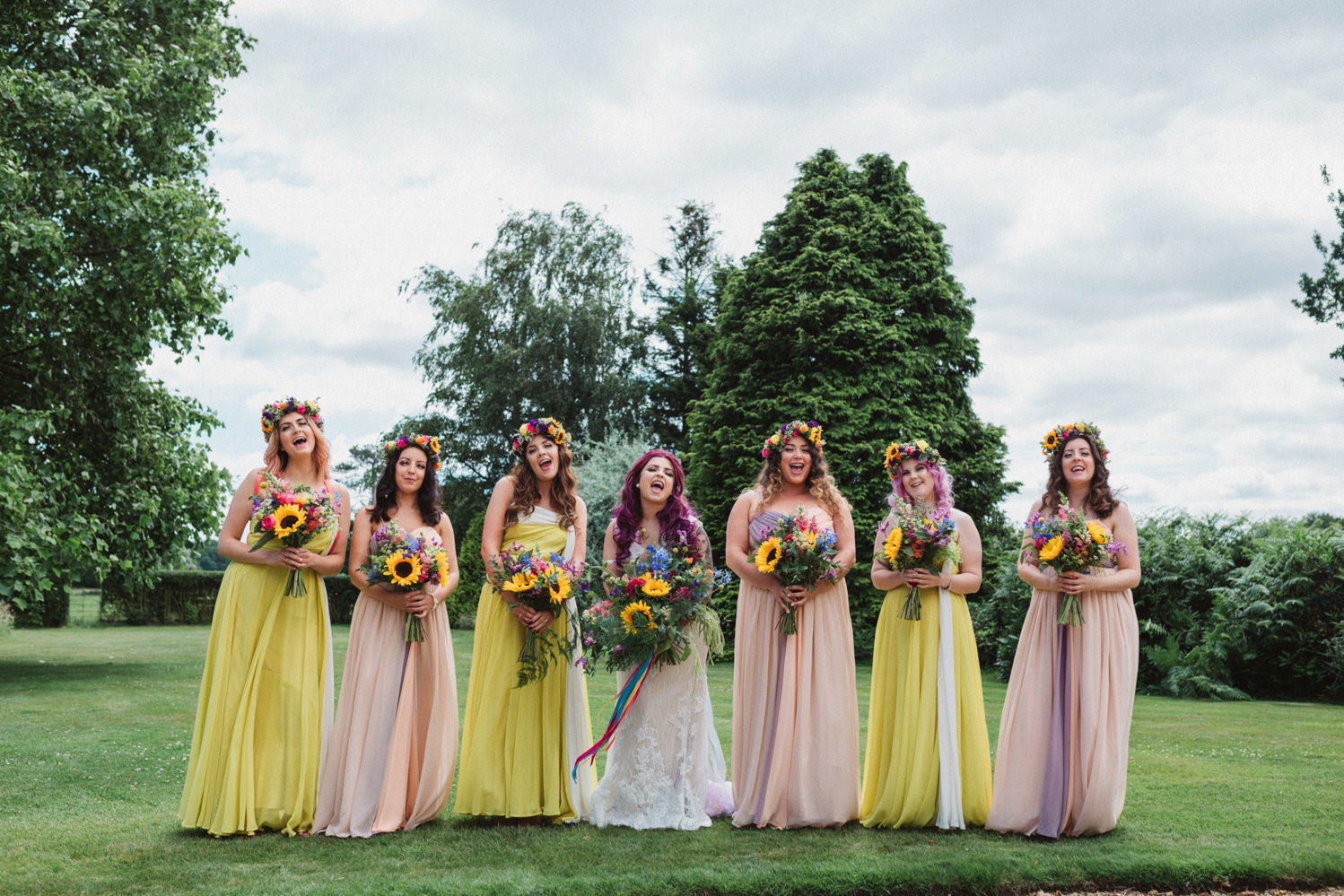 Multicoloured laughing Helen Andersons bridesmaids before her outdoor festival wedding at Godwick Hall