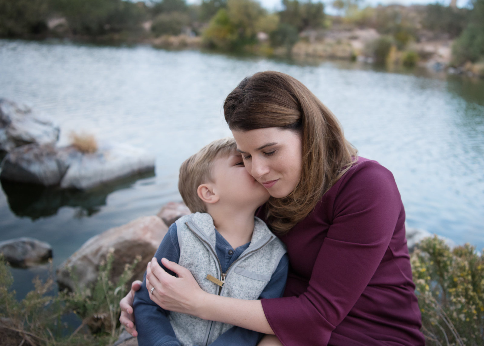 boy kissing his mom's cheek by a lake