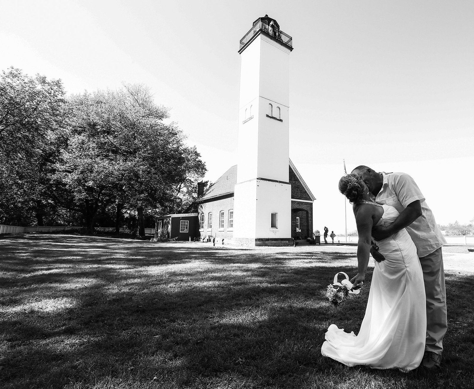Bride and groom kiss in front og lighthouse on Presque Isle State Park