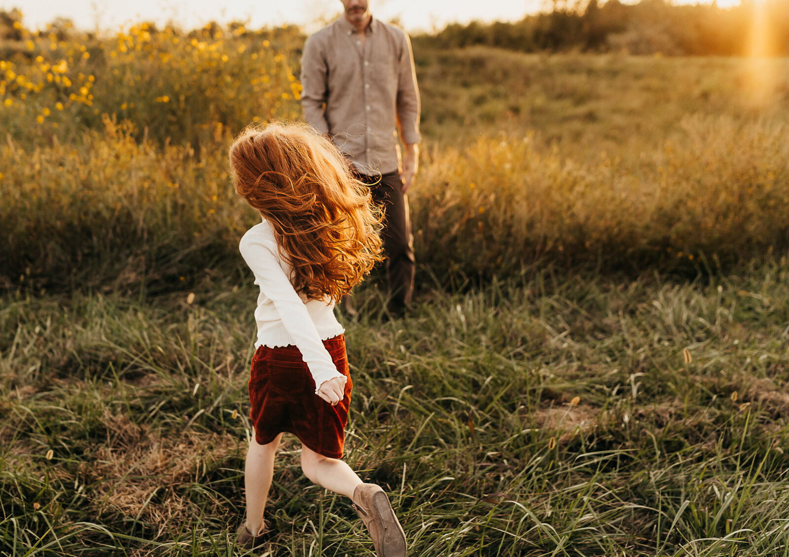 girl with red hair running through a field