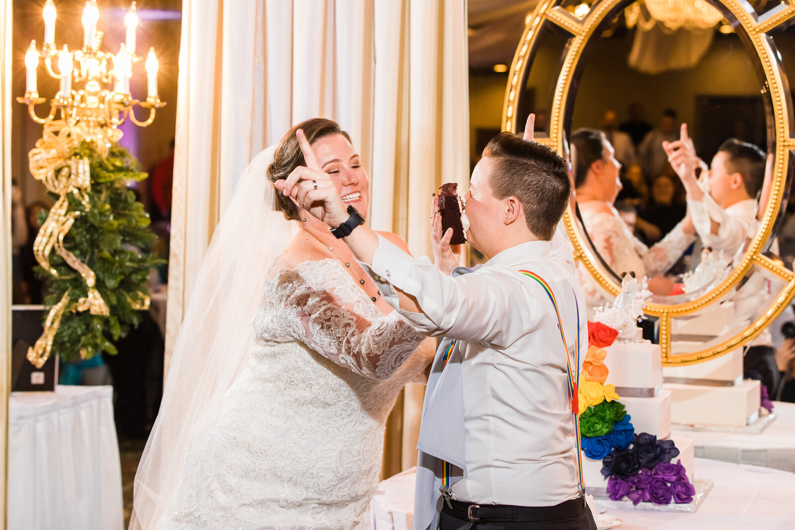 Bride smashing wedding cake into her wife's face at their STL LGBT wedding