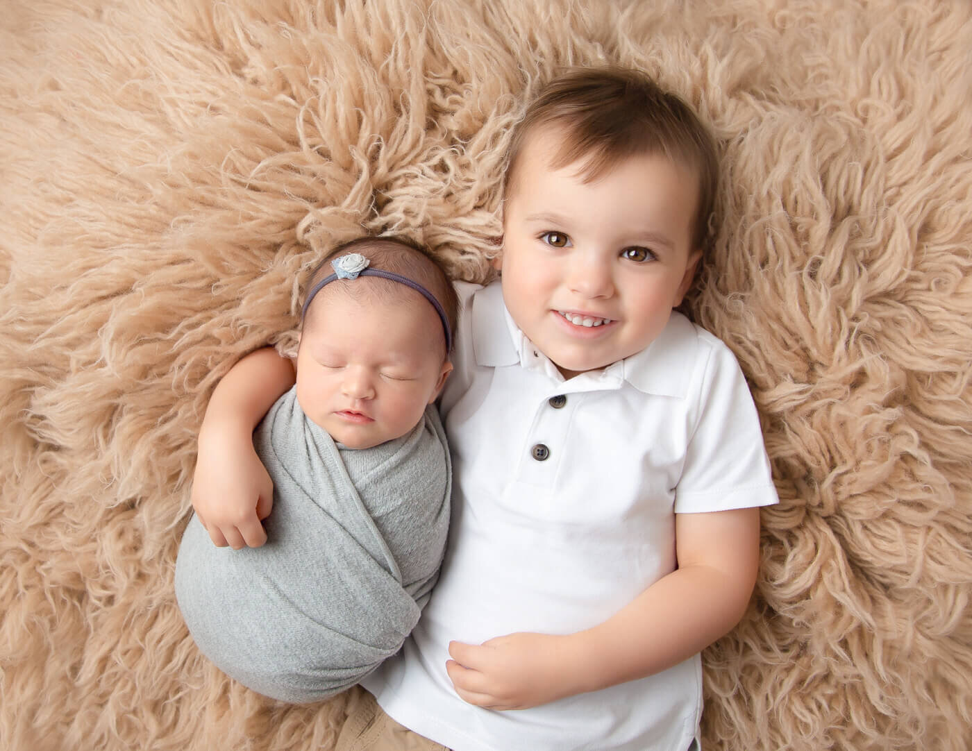 Newborn girl and brother posing in Rochester, NY