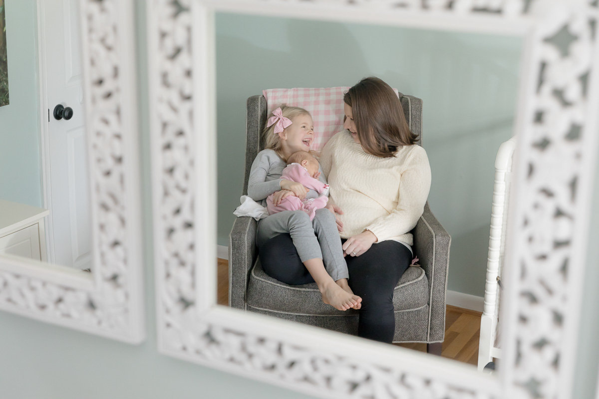 mom and daughter laugh together in mirror at lifestyle newborn photo session