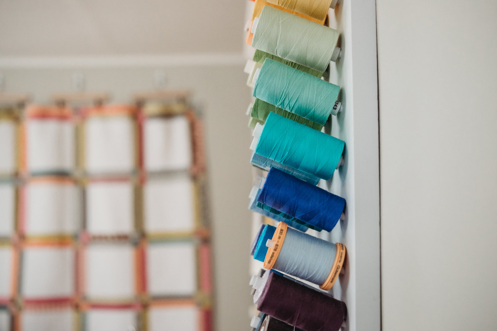 spools of colorful thread in quilting room