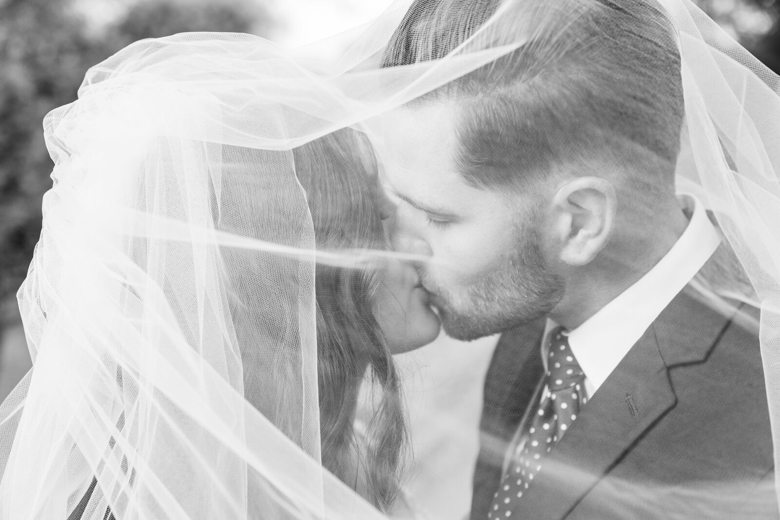 Newlyweds-kiss-under-the-veil-at-their-st-mary's-golf-club-wedding
