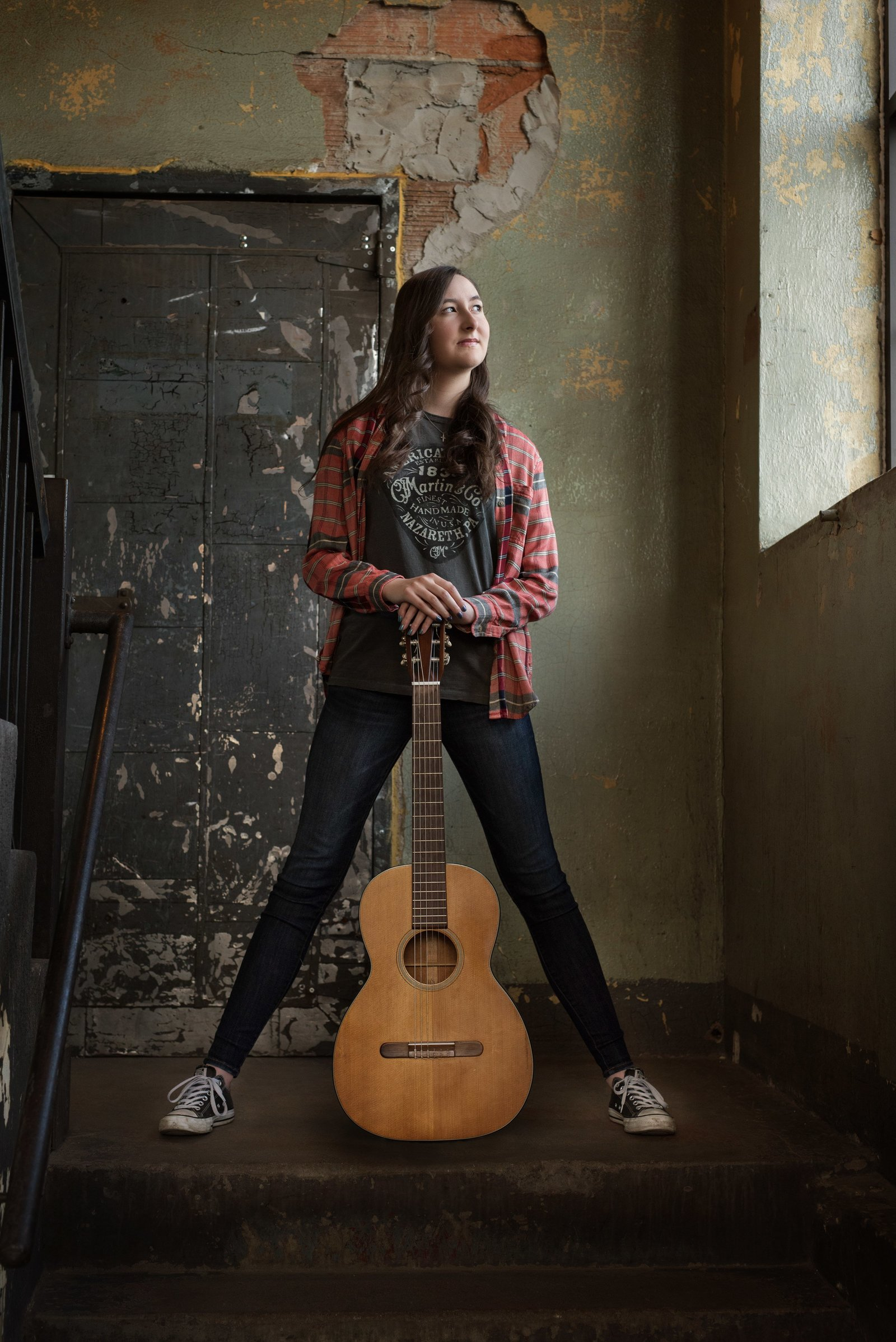 Senior picture of girl in grungy scene with guitar