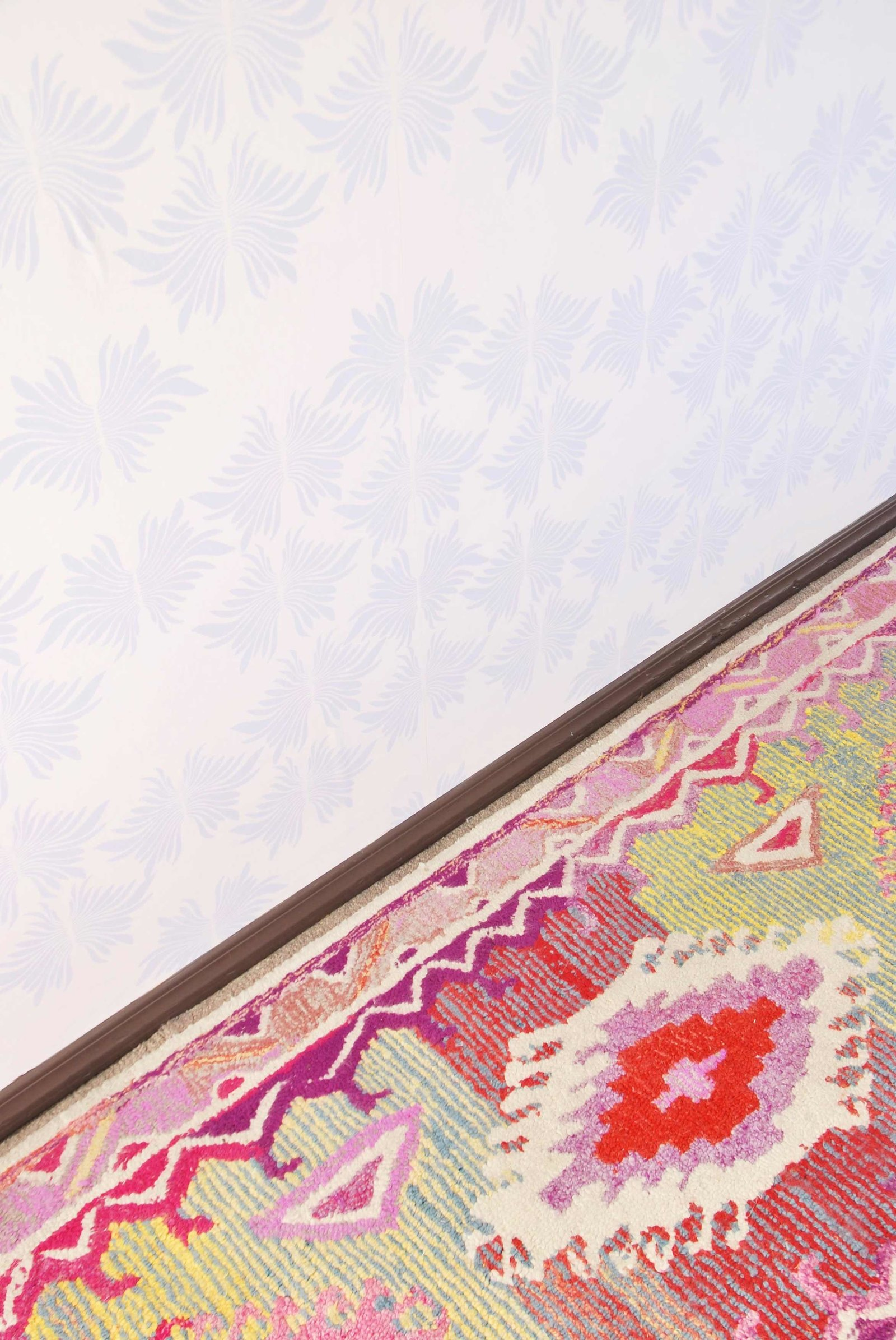 A colorful patterned rug next to an abstract wall papered wall.