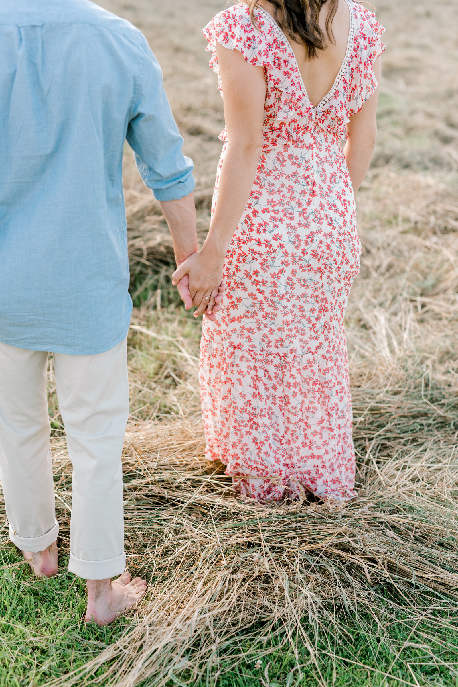 Erie Engagement Photographer- couple walking through a field