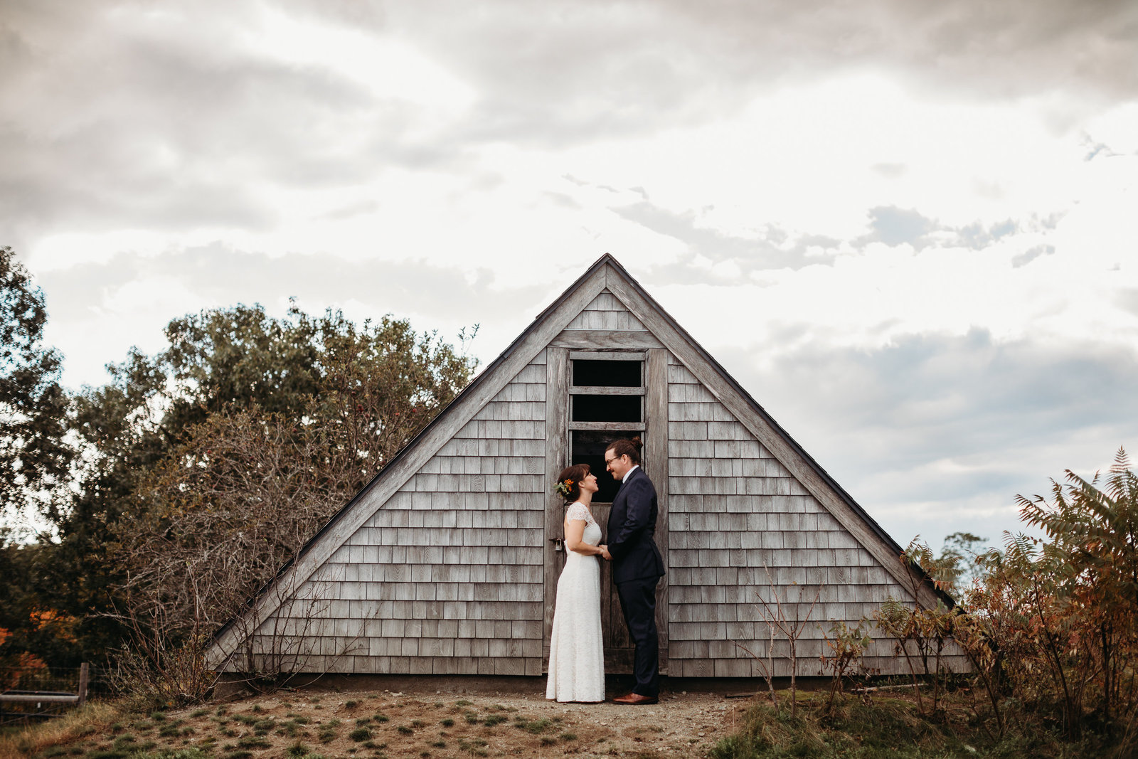 wedding couple portraits next to A frame structure in massachusetts