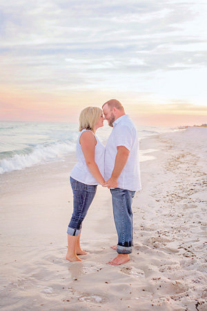 husband and wife standing face-to-face on the beach