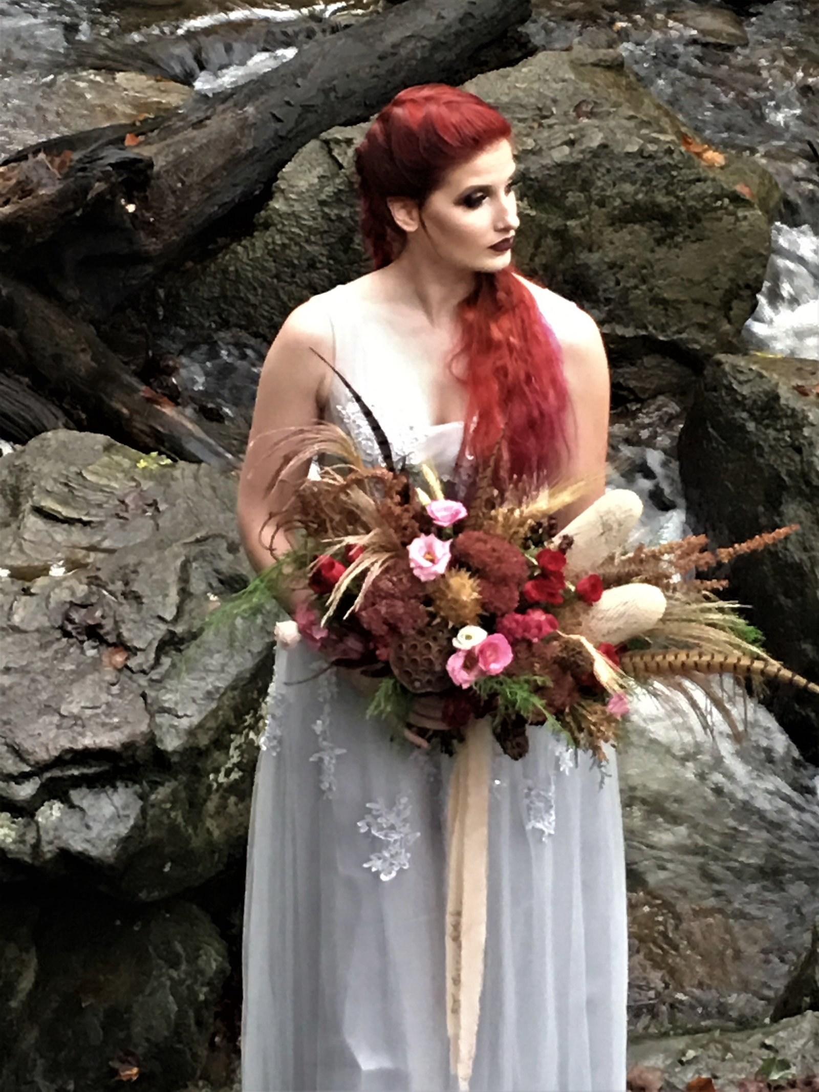 Bohemian bridal bouquet with natural flowers , feathers, and seed pods
