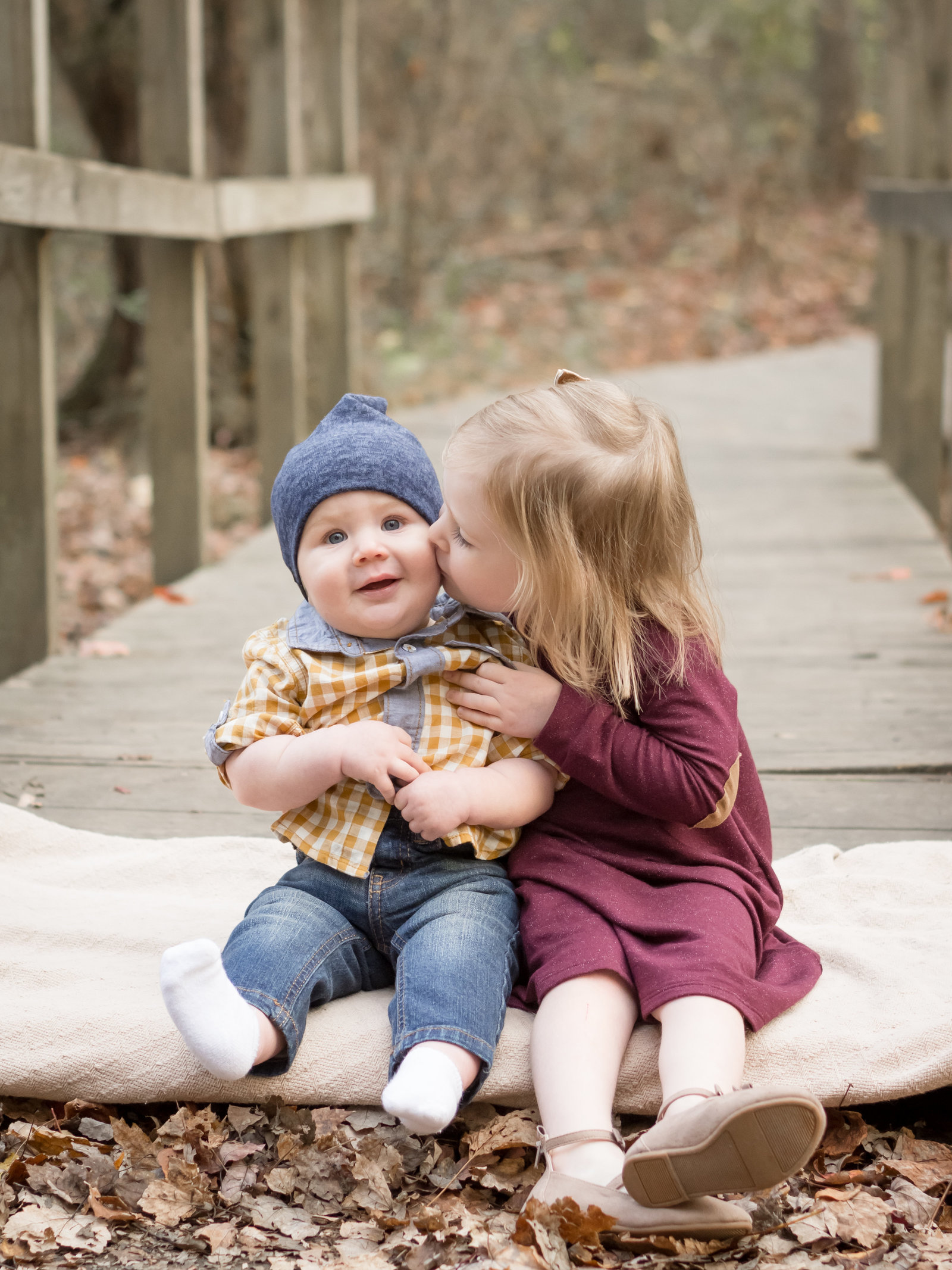 Two little kids snuggled up on the bridge. Big sister kissing little brother on the cheek