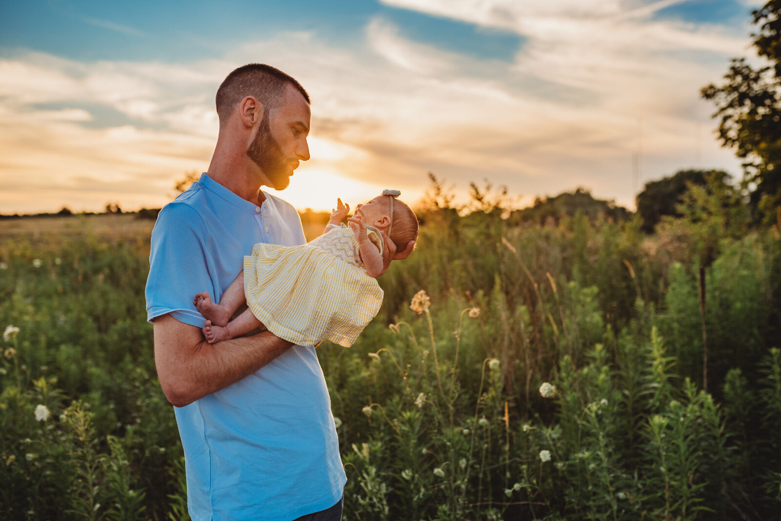 Father looking down at his newborn daughter at sunset in Oshawa