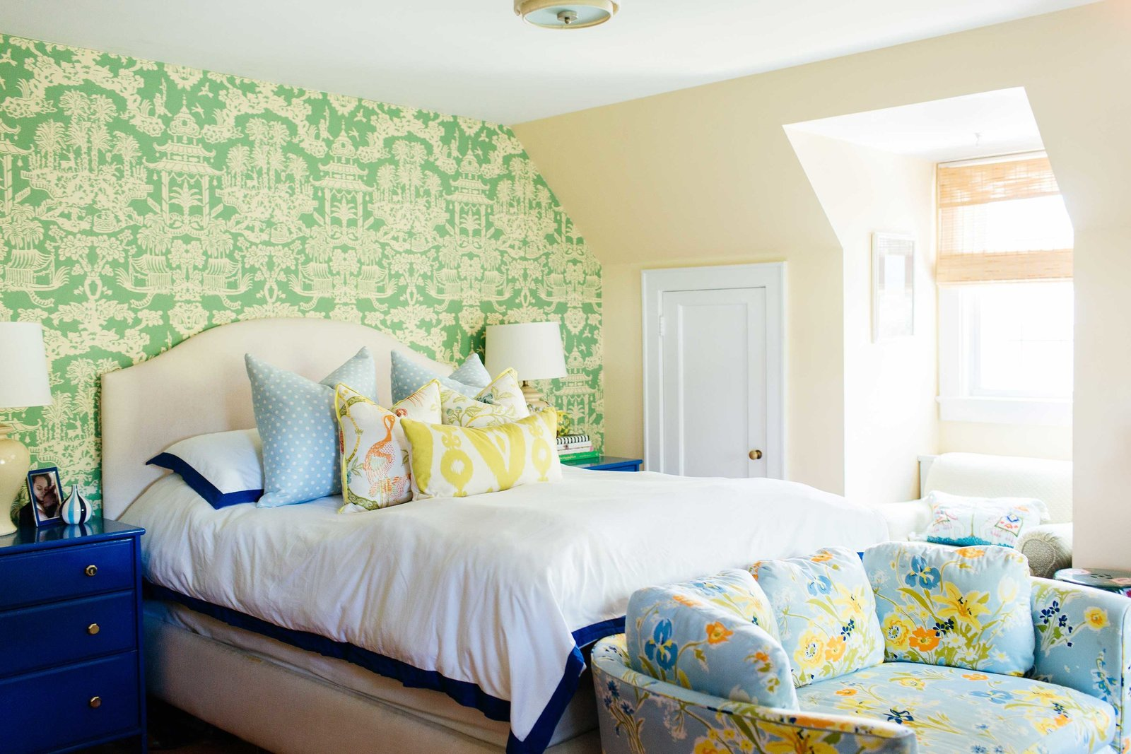 A white bed and blue end tables in front of a green wall papered wall.