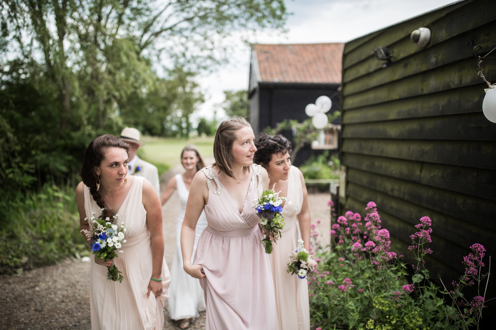 Bridesmaids peer round the corner whilst holding bouquets outside a barn venue in Norfolk.