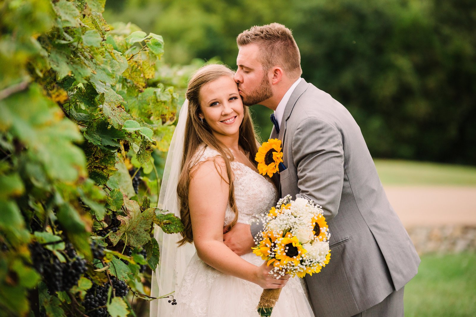 Bride and Groom, Whitney and Derik, pose next to full green vineyards at Chaumette Winery.