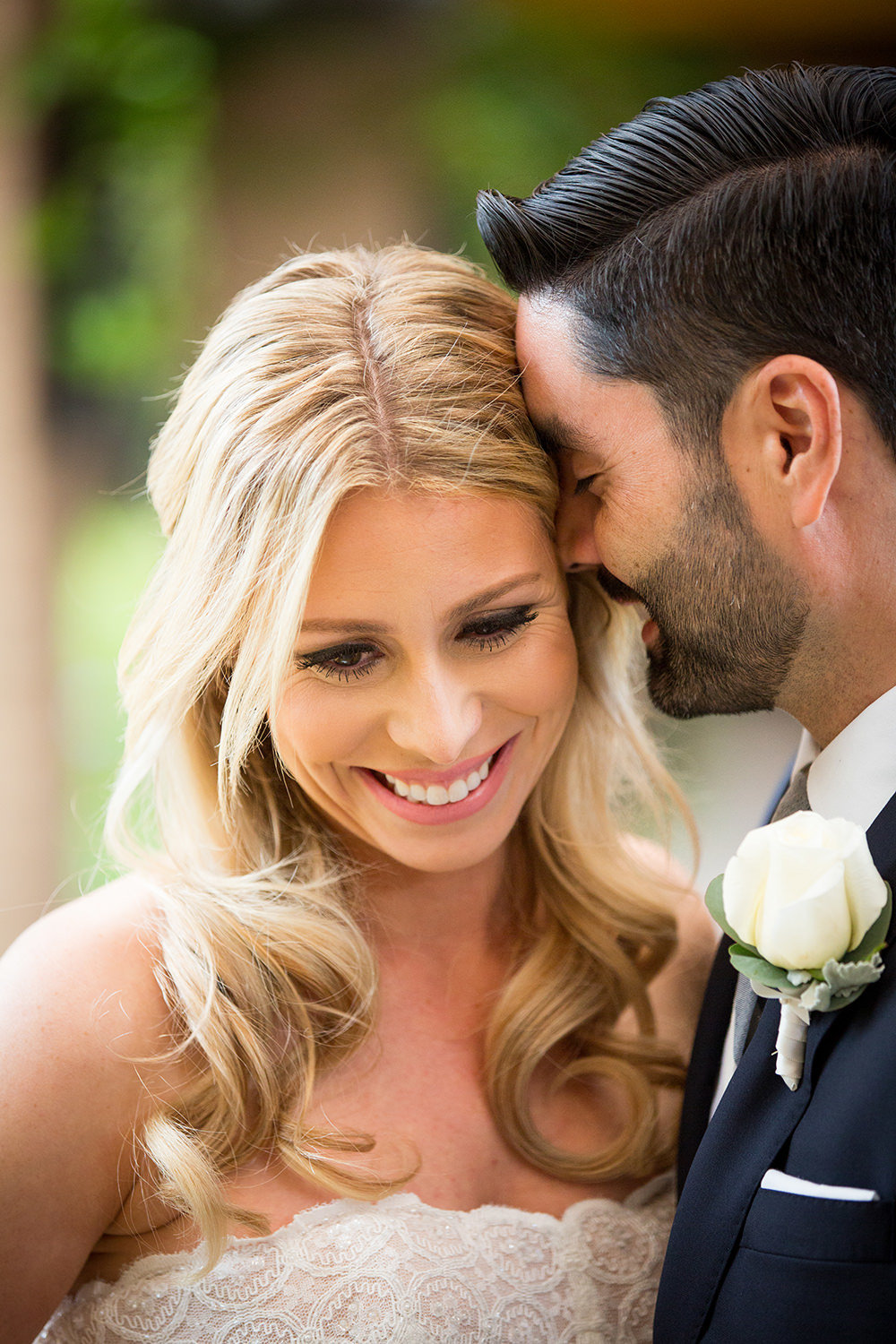 closeup of bride with groom kissing cheek