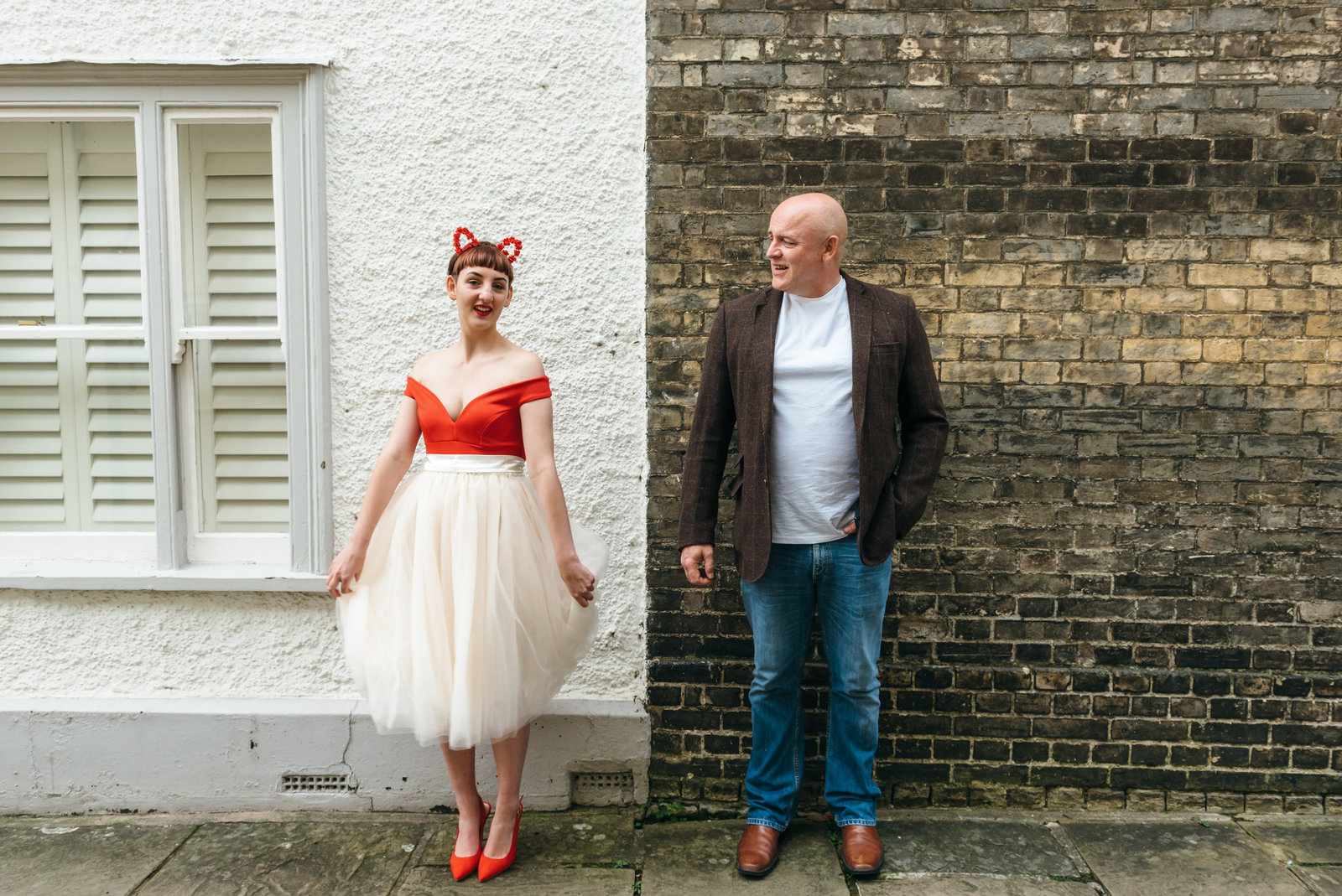 Lisa and Neil stand in front of a brick wall in Norwich. Lisa is holding her skirt and looking at the camera and Neil is looking at her and smiling.