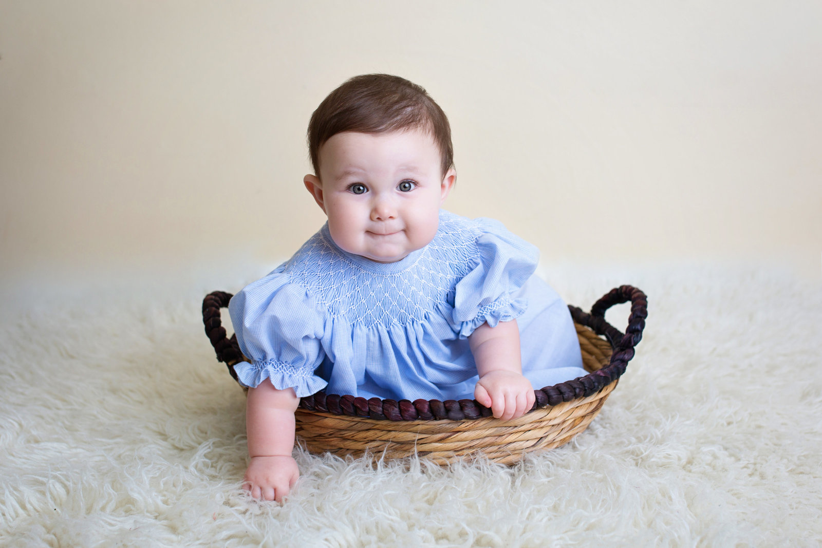 baby girl in blue dress sitting in a basket