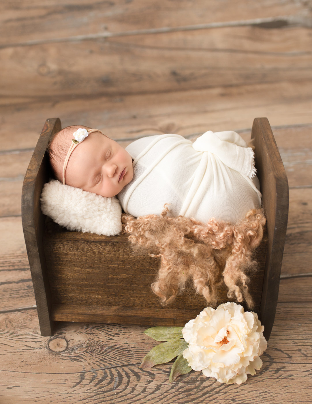 Sleepy newborn girl posed in our Rochester, NY studio.