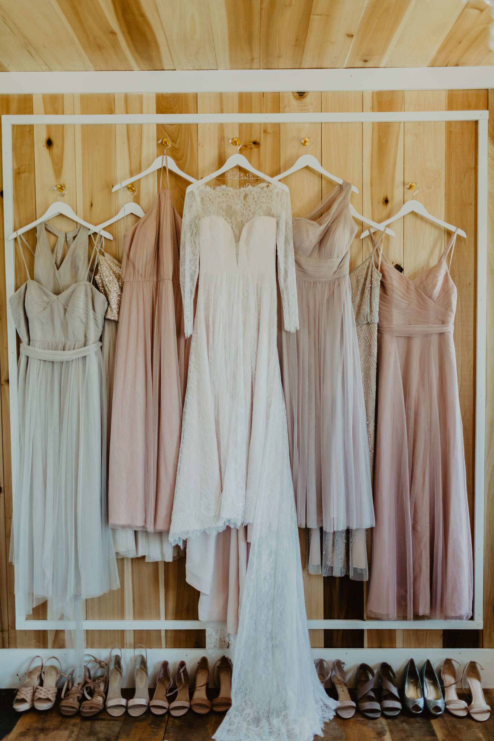Bride and Bridesmaid dresses hanging on rustic bridal suite wall with shoes lined beneath them at Allenbrooke Farms.