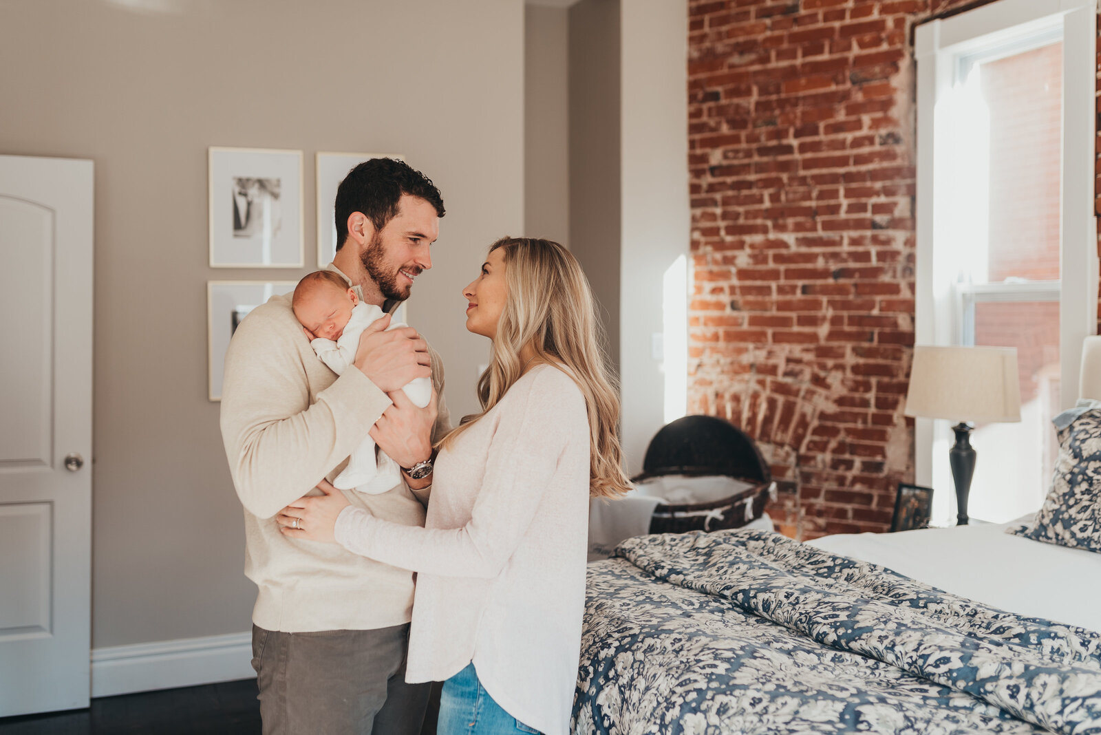 couple holding baby in bedroom