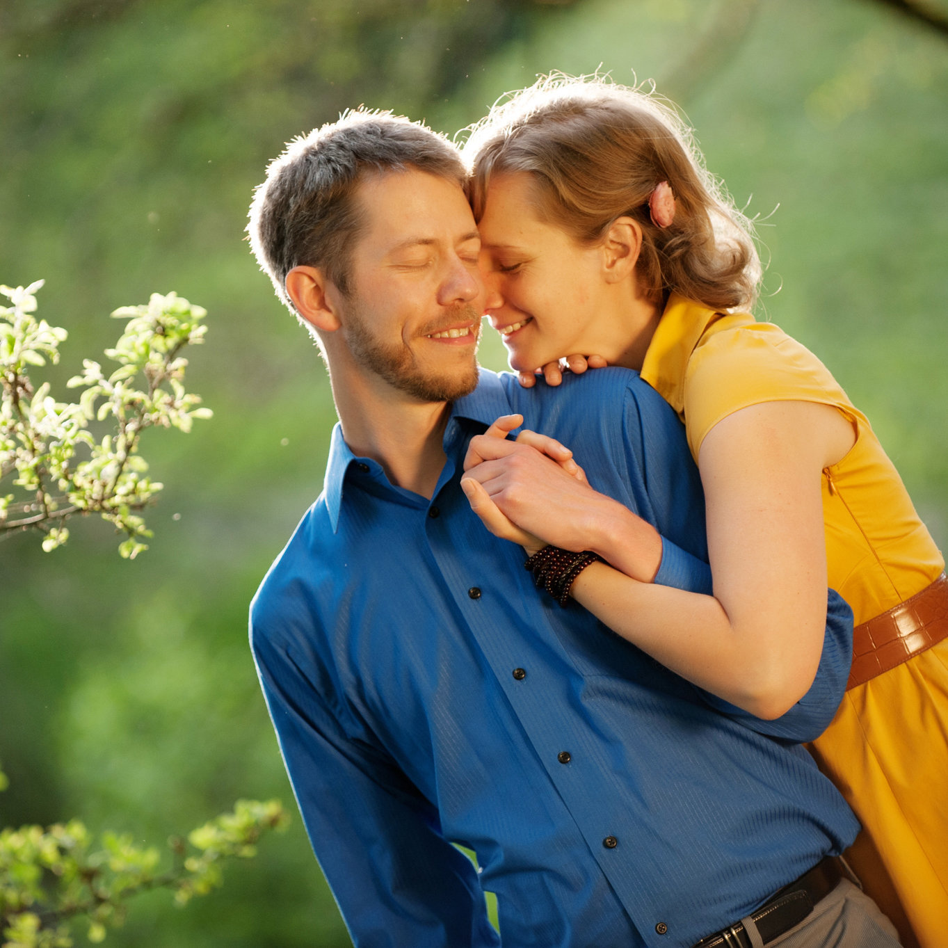 a woman in a yellow dress and a man in a bright blue shirt hug in the sunlight