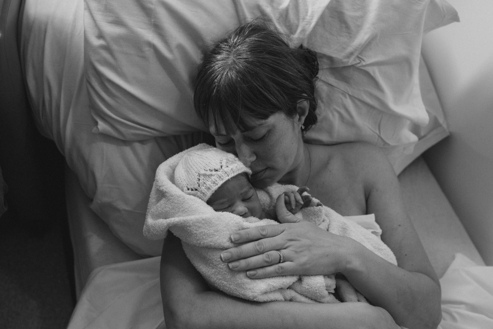 Black and white Documentary photograph of Ipswich mum holding newborn baby minutes after birth