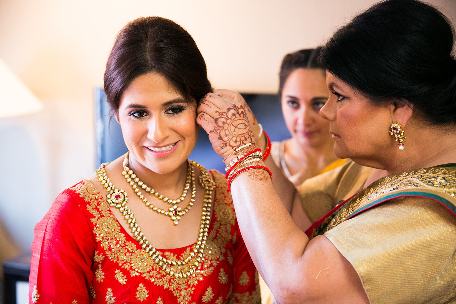 A bride is helped with her earrings by her mother