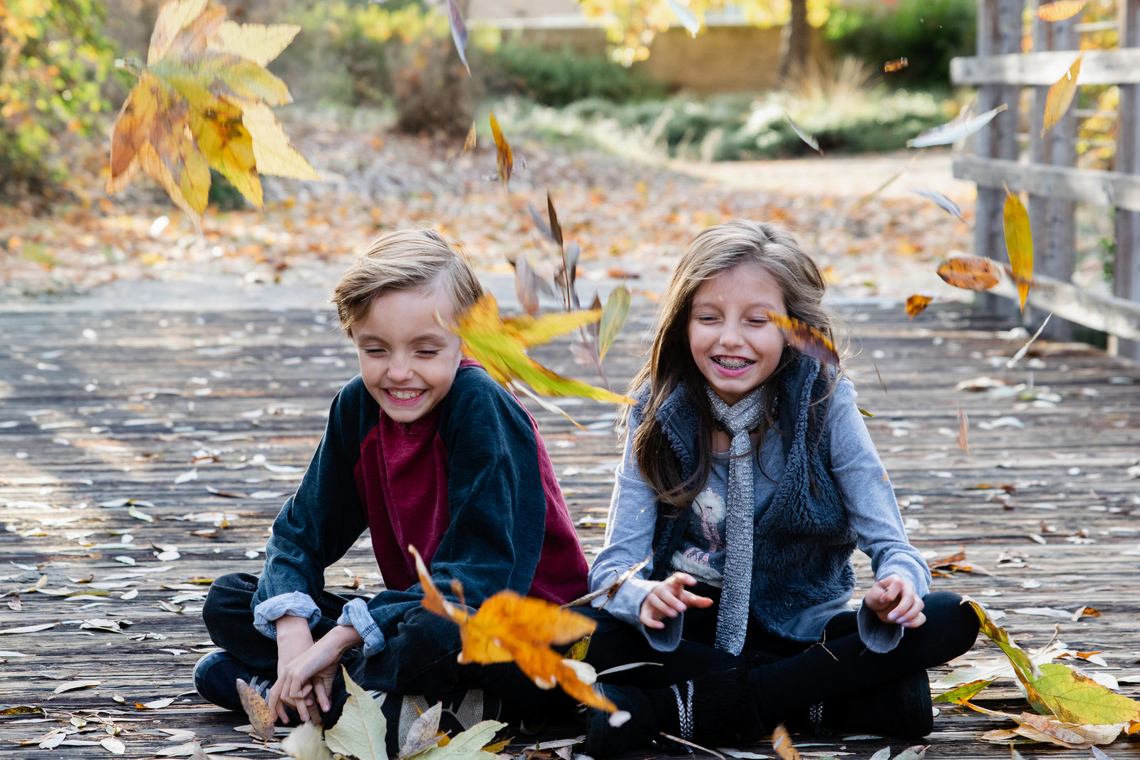 young brother and sister sitting on bridge with leaves falling on them