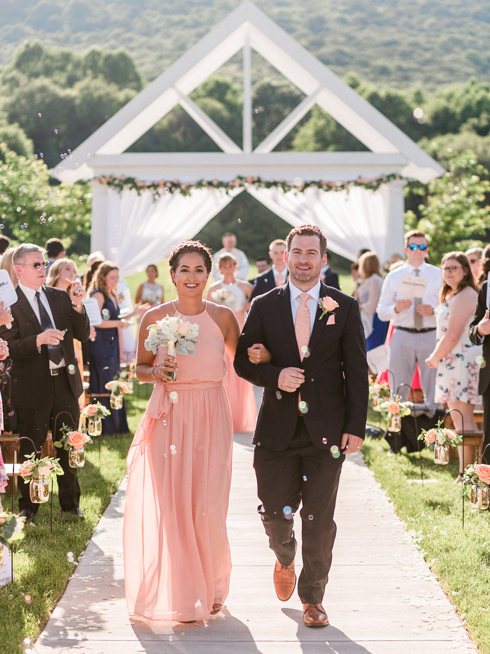 Bridesmaid in pink dress walks with groomsmen up the aisle at Springfield Manor Maryland