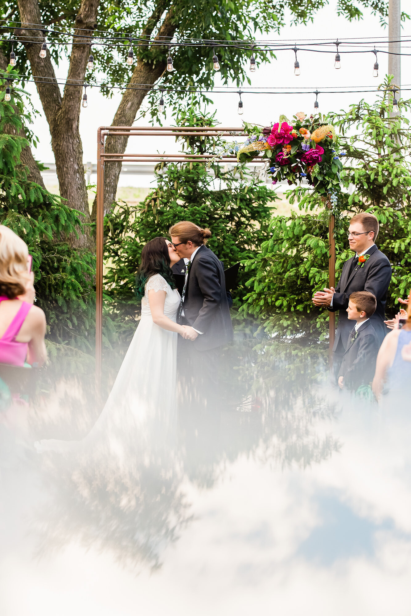 Creative photo of bride and groom's first kiss at their outdoor Wild Carrot wedding ceremony