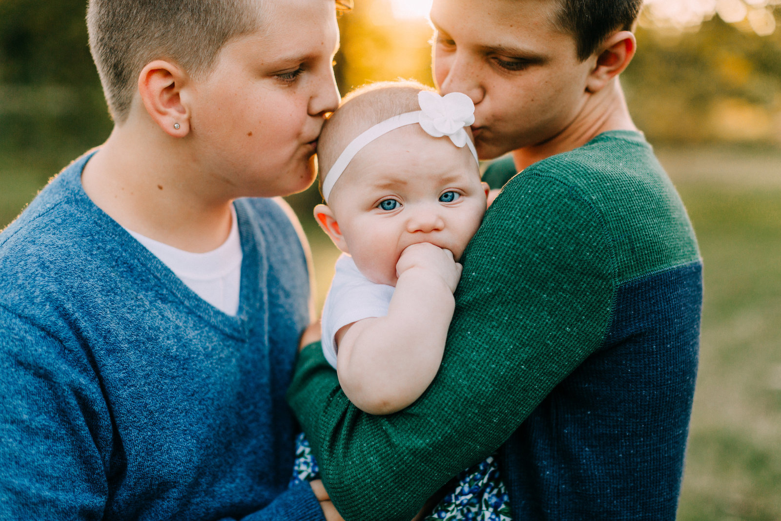 Big borthers kissing baby sister at family session in Forest Park St Louis