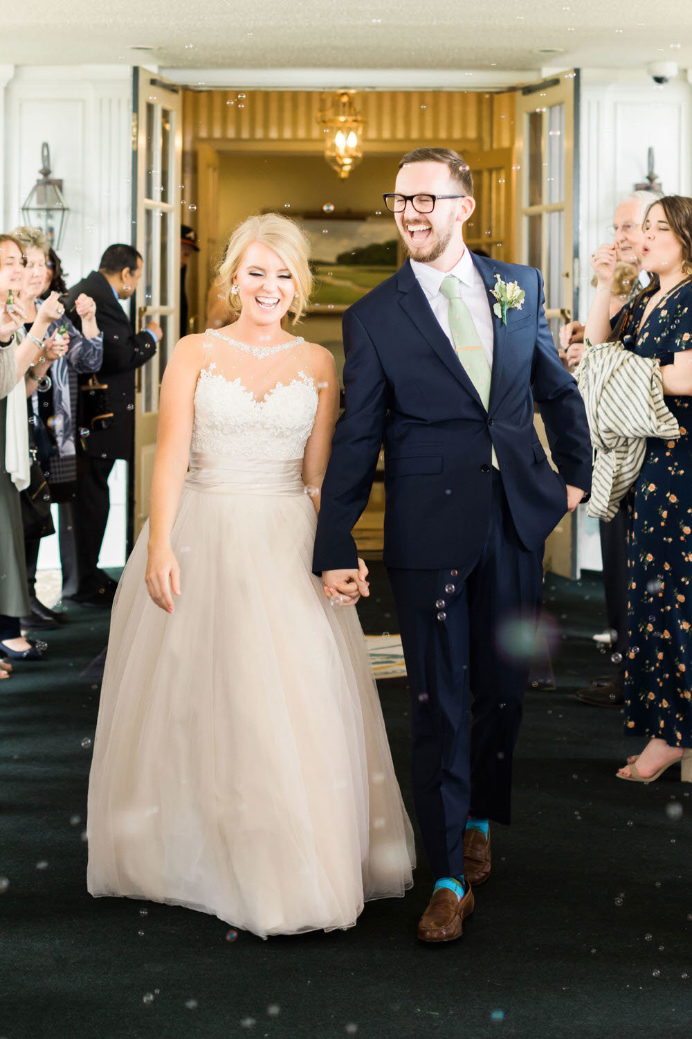 bride and groom laughing while walking through guests