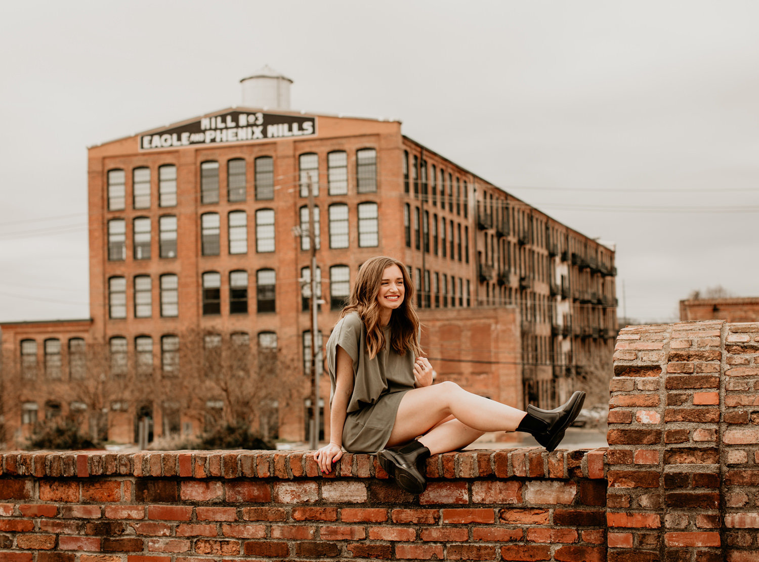 girl sitting on brick wall