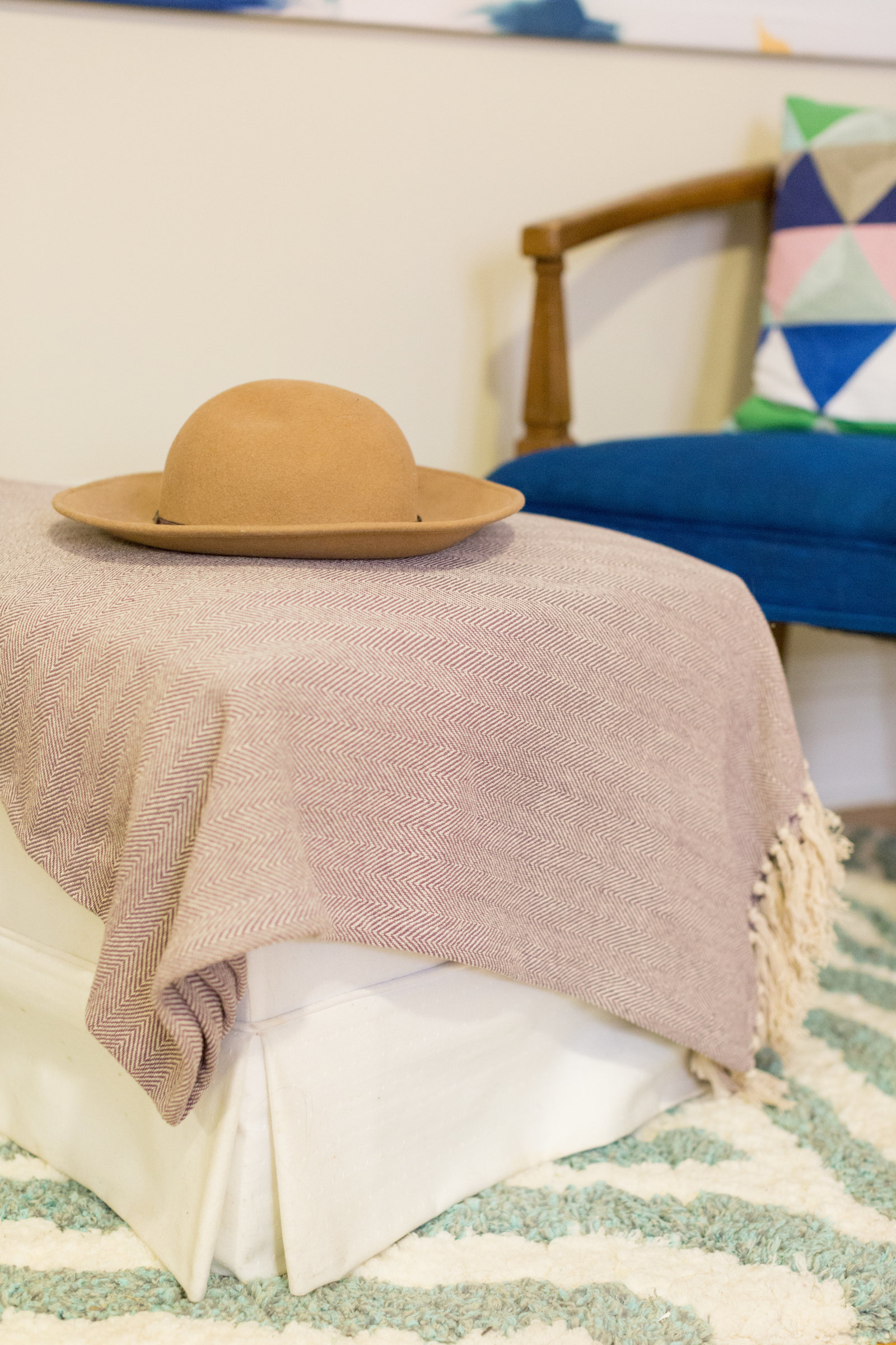 A tan sued hat on a blanket on an ottoman.