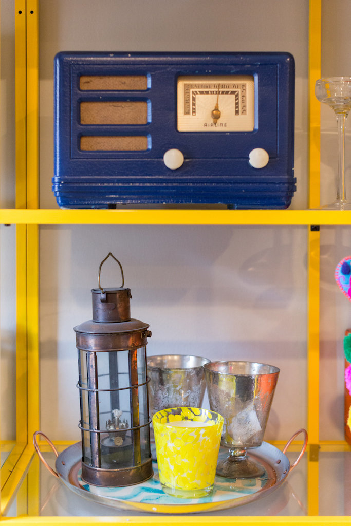 Yellow and glass shelves with a blue vintage radio, lantern, and dishes.